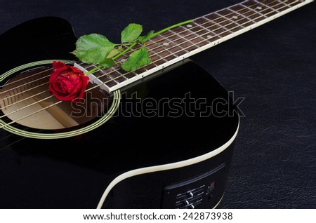 Acoustic guitar and red rose on black - stock photo