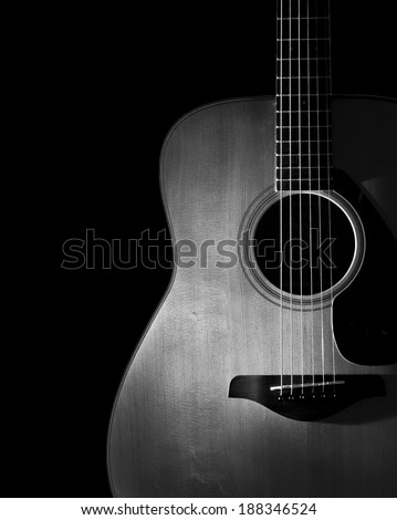 acoustic guitar detail on black background - stock photo