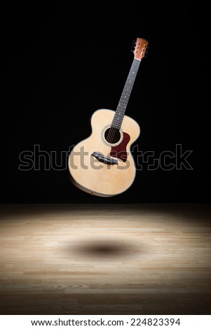 Acoustic guitar floating in the air