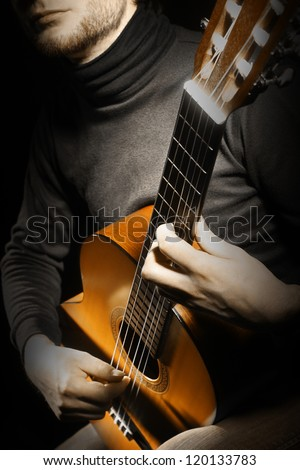 Acoustic guitar guitarist playing details. Musical instrument with musician hands. Focus is on the hand with instrument