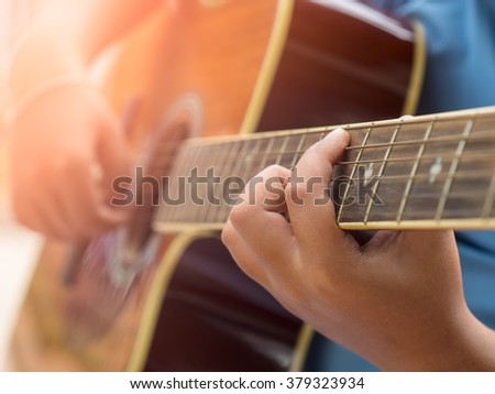 Acoustic guitar guitarist playing. Musical instrument with  hands Vintage Style