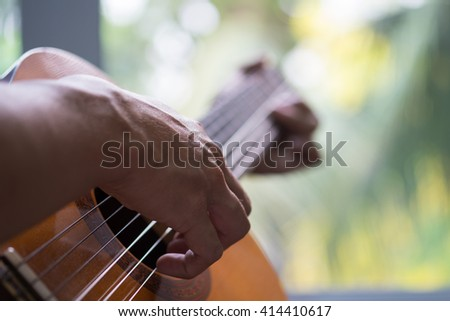 Acoustic guitar guitarist playing. Musical instrument with performer hands.