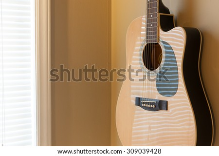 Acoustic guitar hanging on the wall close up - stock photo