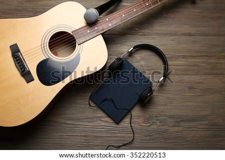 Acoustic guitar, headphones, notebook and microphone on wooden background