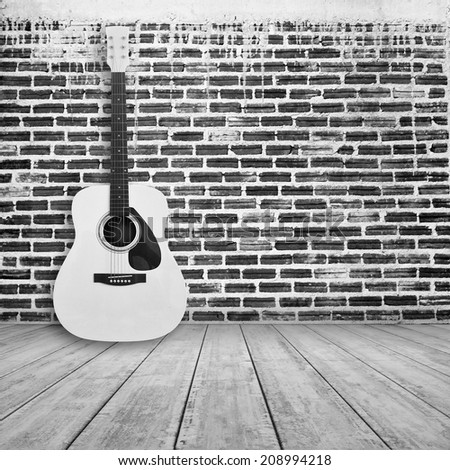 acoustic guitar in empty room with brick wall background - stock photo