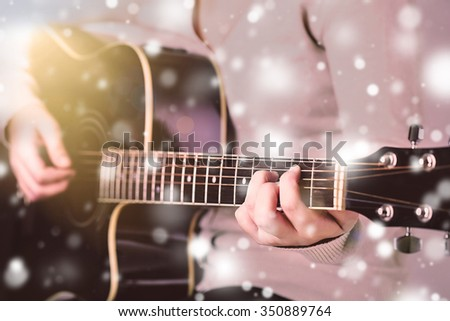 Acoustic guitar in female hands over snow effect - stock photo
