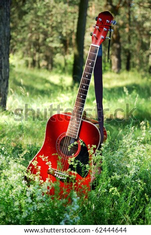 acoustic guitar in the green grass - stock photo