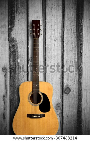 Acoustic guitar is on the wooden background.