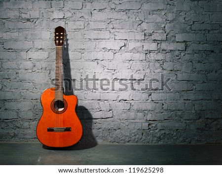Acoustic guitar leaning on grungy gray brick wall - stock photo