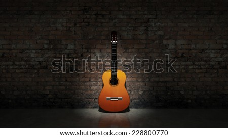 Acoustic guitar leaning on grungy wall - stock photo