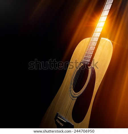acoustic guitar on a black background in the rays of light - stock photo