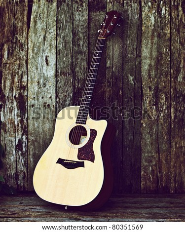 Acoustic guitar on a grunge wood backdrop with copy space.