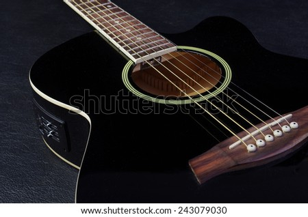 Acoustic guitar on black - stock photo