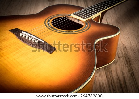 Acoustic Guitar on top of a wood table - stock photo