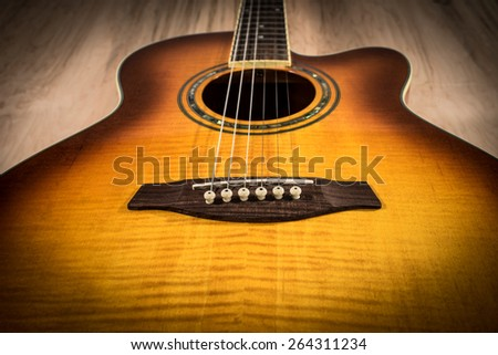 Acoustic Guitar on top of a wooden table - stock photo