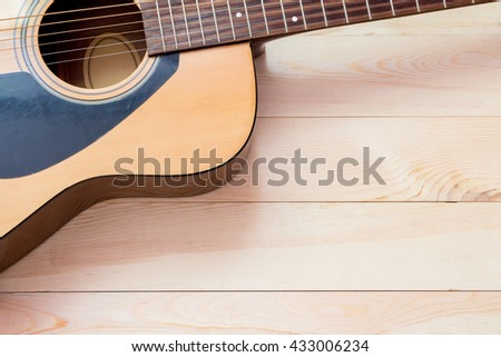 Acoustic guitar on wood desk background