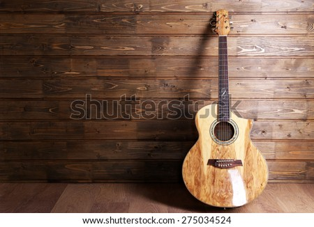 Acoustic guitar on wooden background - stock photo