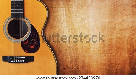 Acoustic guitar resting against a blank grunge background with copy space - stock photo
