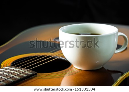 Acoustic guitar with a cup of coffee  - stock photo