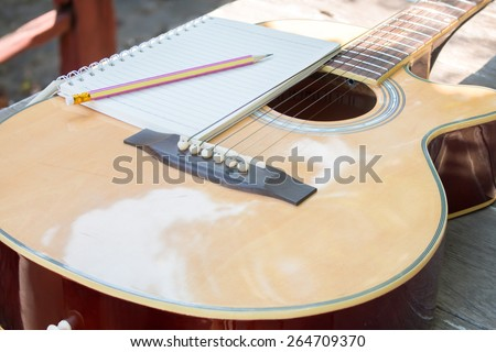 Acoustic Guitar with notebook  in garden - stock photo