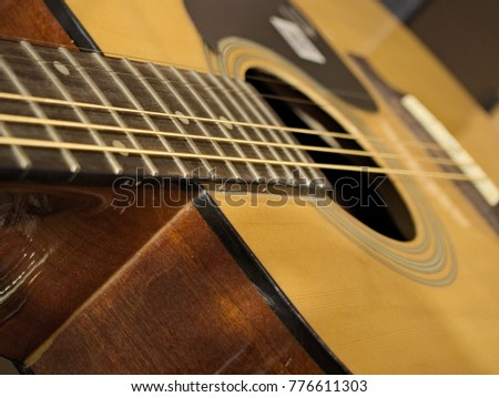 Acoustic guitar with yellow wooden body and silver nylon strings.