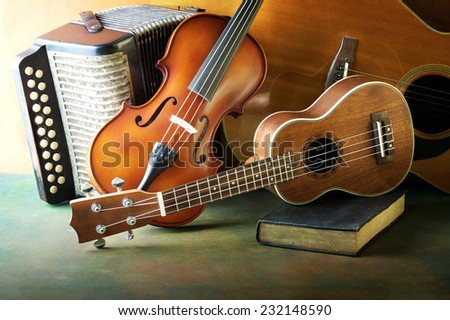 Acoustic musical instruments guitar ukulele violin and accordion still life style - stock photo