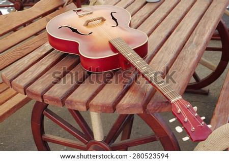 Acoustic vintage guitar in the tavern - stock photo