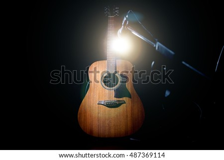 Acoustic wooden a guitar over black background. Music and concert concept.