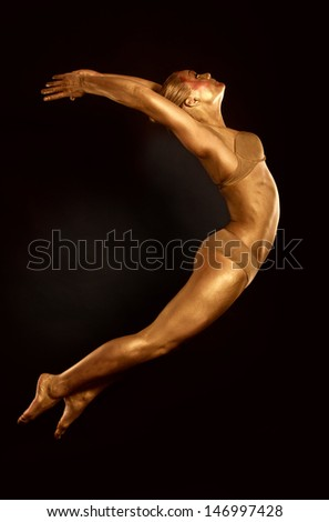 acrobat dancer toned in gold  jumping over black background