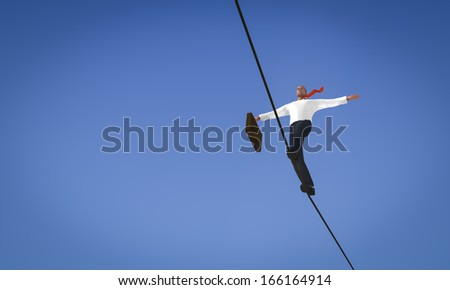 Acrobat tightrope businessman, with briefcase in hand - stock photo