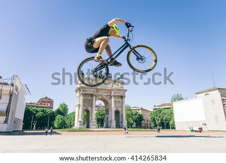 Acrobatic biker jumping with his bicycle on the streets - Bmx bicycle rider tricking outdoors - stock photo