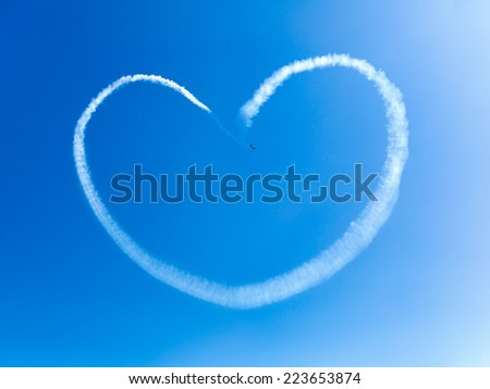 Acrobatic plane in action making hart on blue sky