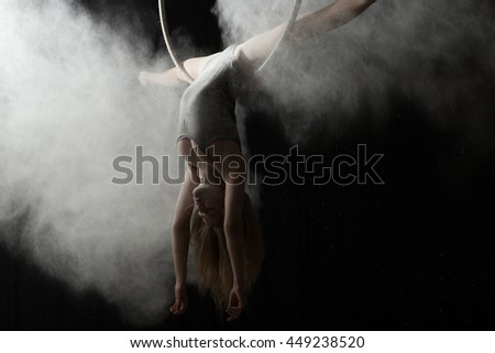 Acrobatic woman doing gymnastic cross twine on aerial hoop with flour - stock photo