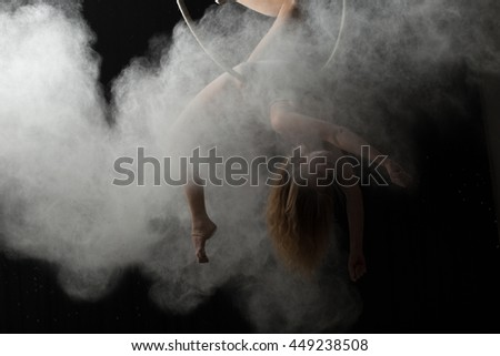 Acrobatic woman doing gymnastic element on aerial hoop with sprinkled flour - stock photo