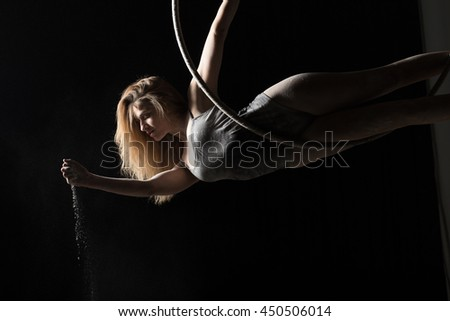 Acrobatic woman hunging on aerial hoop and pouring flour - stock photo