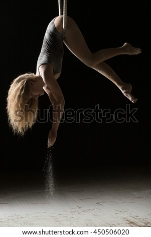 Acrobatic woman hunging on aerial hoop and pouring flour