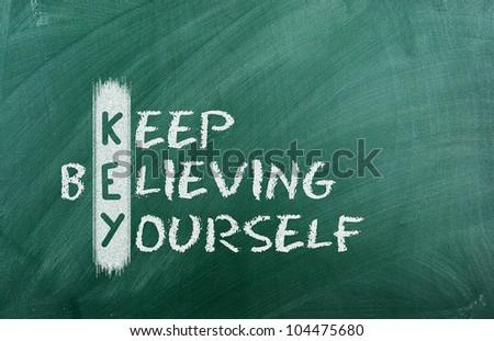 Acronym of KEY. Believe in yourself written in chalk on a blackboard . - stock photo