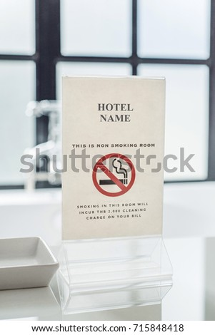 Acrylic non smoking room sign in white room with window behind