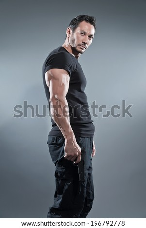 Action hero muscled man holding a gun. Wearing black t-shirt and pants. Studio shot against grey. - stock photo