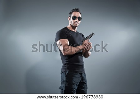 Action hero muscled man holding a gun. Wearing black t-shirt with pants and sunglasses. Studio shot against grey. - stock photo