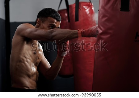 action of a boxing martial arts fighter training on a punching bag in the gym - stock photo