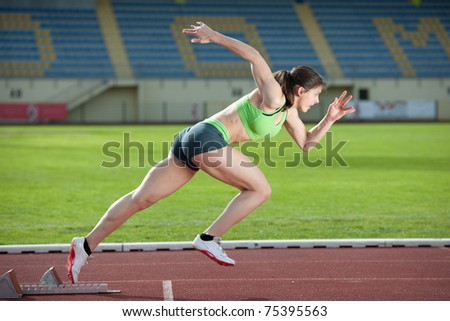 Action packed image of a female sprinter leaving starting blocks on the track. Side view. - stock photo