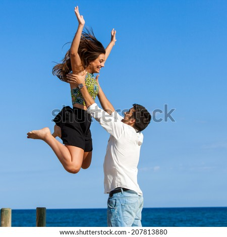 Action portrait of Girl jumping into boys arms at sea side. - stock photo