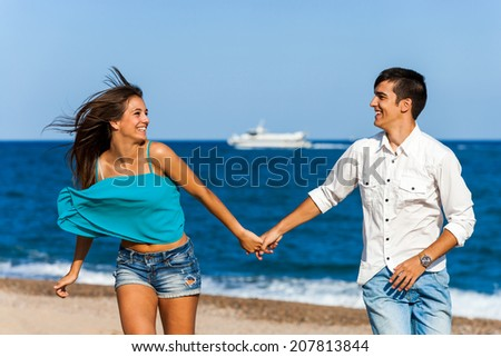 Action portrait of happy teen couple holding hands running on beach. - stock photo