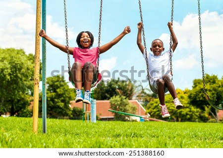 Action portrait of shouting African kids playing on swing in neighborhood.Out of focus houses in background. - stock photo