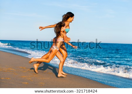 Action portrait of Young girls on holiday. Two women running towards blue sea.