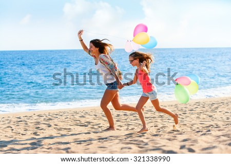 Action portrait of Young girls running with colorful balloons on beach. - stock photo
