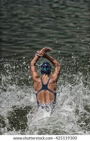 Action shot of a female athlete at the moment of water entry. Shallow depth of field, toned, desaturated, High shutter speed used to capture water splash. Convenient copy space above - stock photo
