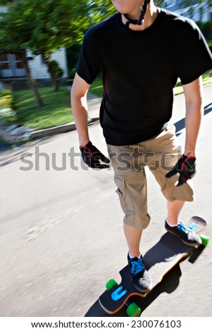 Action shot of a longboarder skating on an urban road. Slight motion blur.