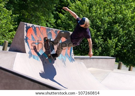 Action shot of a skateboarder skating on a concrete skateboarding ramp at the skate park. Shallow depth of field.